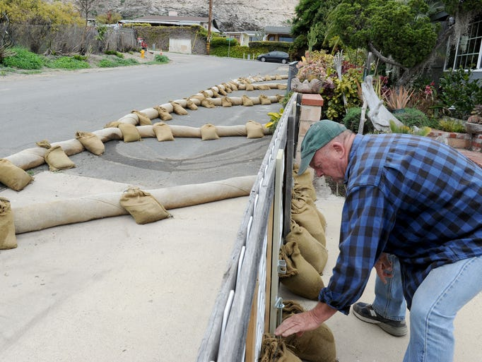Dennis Hall places sandbags around his home in La Conchita
