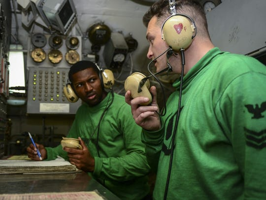 Airman Quadarius Donald, left, and Aviation Boatswain's Mate (Equipment) 1st Class George Pownall man a catapult control room aboard the aircraft carrier USS Nimitz. It was Donald's first deployment with the Navy.