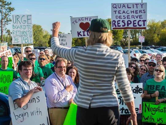 Teachers and their supporters listen as Martha Allen,