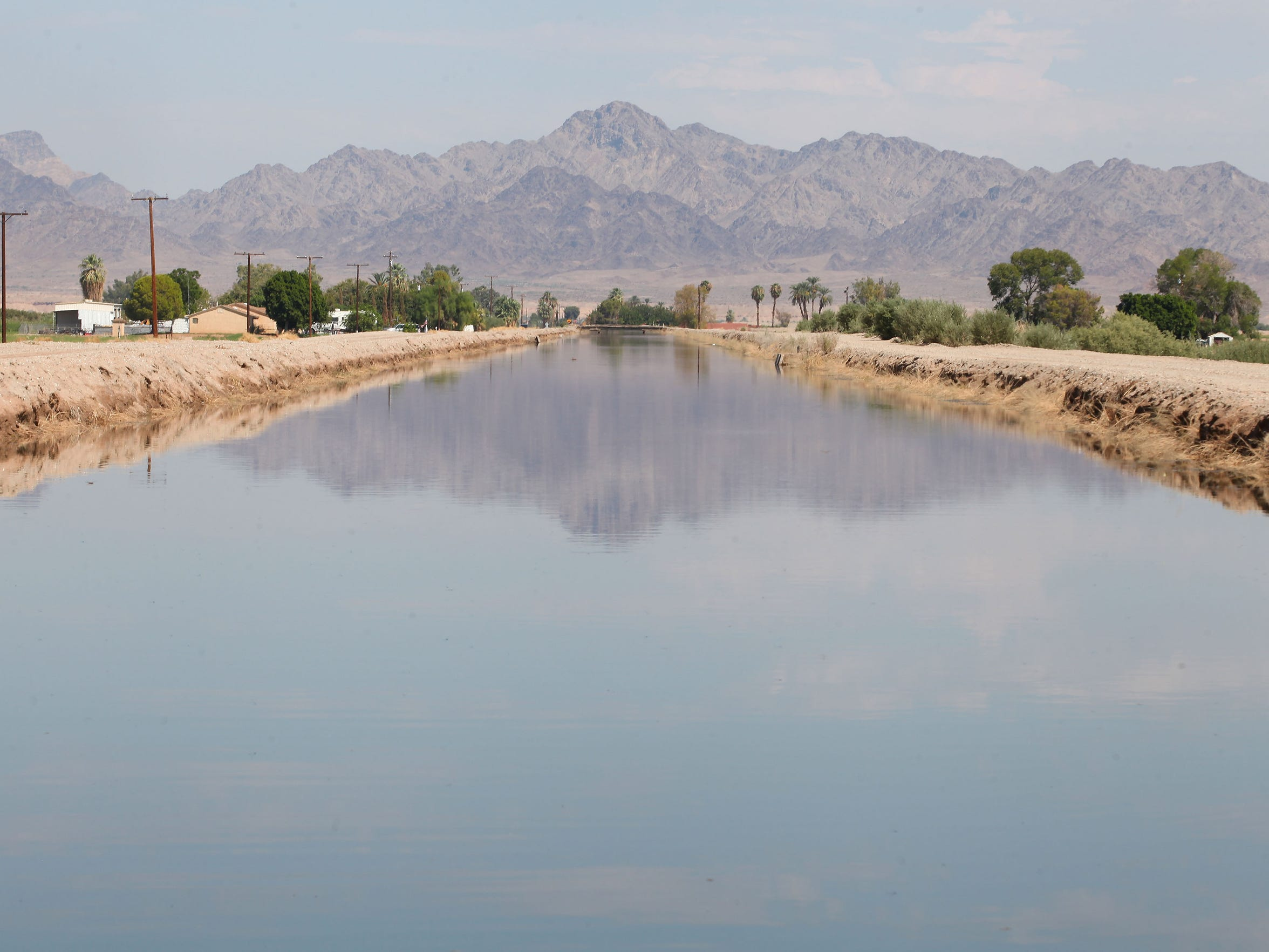 Mountains are reflected in a canal that carries Colorado River water to farmlands in the Palo Verde Valley.