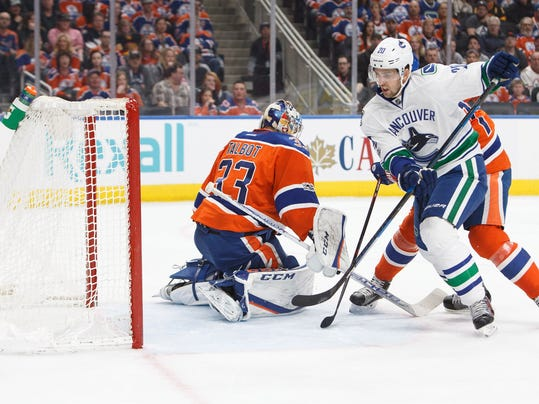 Edmonton Oilers goalie Cam Talbot (33) minds the net as Vancouver Canucks' Brandon Sutter (20) looks for a shot during the first period of an NHL hockey game Saturday, March 18, 2017, in Edmonton, Alberta. (Codie McLachlan/The Canadian Press via AP)