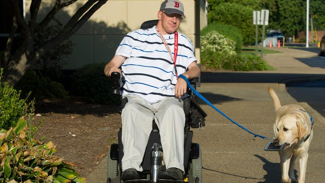 Josh Miller, of Newburgh, leaves a physical therapy session at Easter Seals Rehabilitation Center with his service dog, Noyo, Wednesday, Sept. 7, 2016. In 2005 Miller suffered a C5 vertebrae spinal cord injury causing partial paralysis in his limbs, he has worked with service animals for over 10 years.
