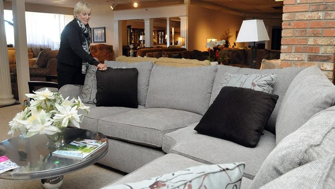 Caroline Taylor straightens pillows on a couch in the main showroom Tuesday at Colonial Heights Furniture. The furniture store has announced a going-out-of-business sale.