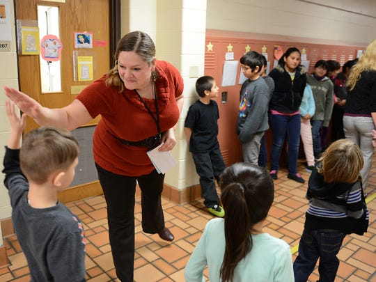 Fourth grade bilingual teacher Ann Klapatch greets students in the hallway Thursday at Nicolet Elementary School.