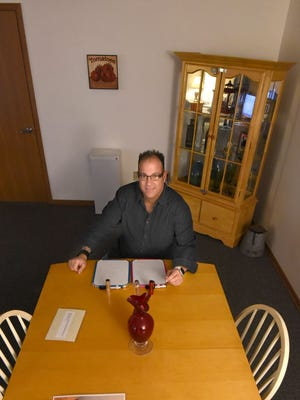 Clues Escape Room owner Steve Rotermund sits at the table where guests will discuss clues and possibly solve a mystery in Mt. Gilead.