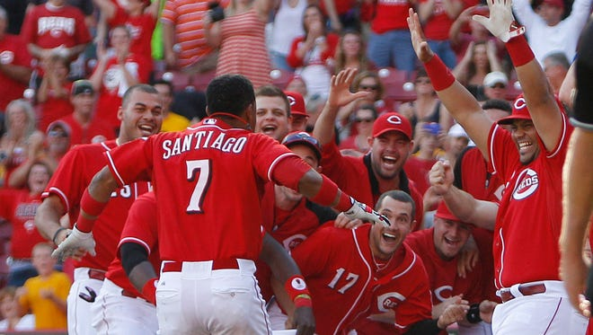 Cincinnati Reds third baseman Ramon Santiago (7) is greeted by teammates after hitting the game winning grand slam walk off home run during the tenth inning.