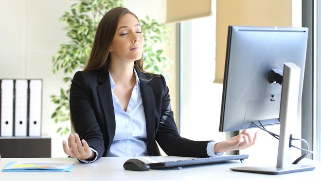 Carefree businesswoman relaxing doing yoga exercises at office