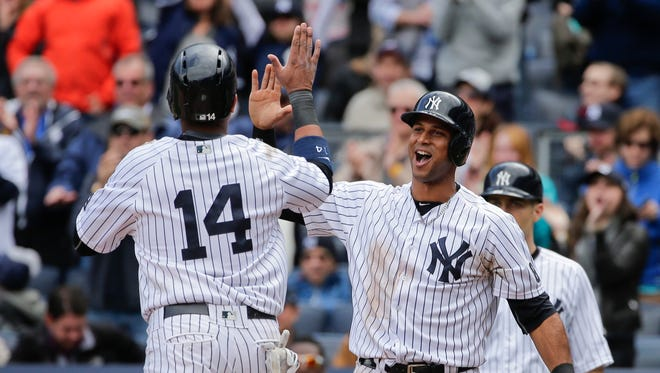 New York Yankees' Aaron Hicks, right, celebrates with teammate Starlin Castro (14) after they scored on a double by Carlos Beltran during the fifth inning of a baseball game against the Boston Red Sox, Saturday, May 7, 2016, in New York.
