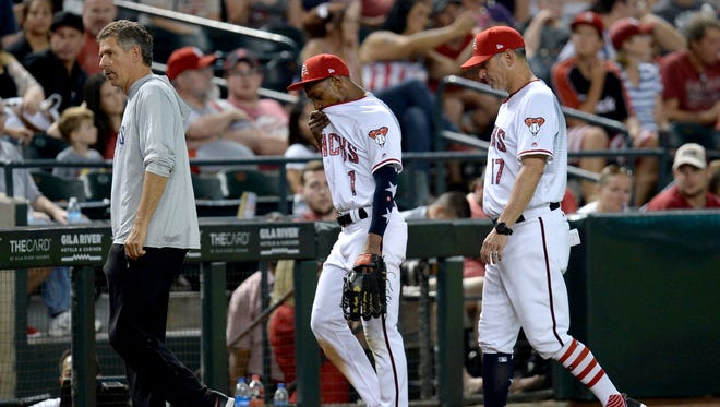 Jul 4, 2018; Phoenix, AZ, USA; Arizona Diamondbacks center fielder Jarrod Dyson (1) leaves the game with an apparent injury as he is flanked by manager Torey Lovullo (right) and head trainer Ken Crenshaw (left) during the seventh inning against the St. Louis Cardinals at Chase Field. Mandatory Credit: Joe Camporeale-USA TODAY Sports
