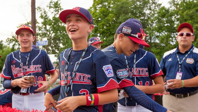 The Maine-Endwell Little League team, representing the Mid-Atlantic Region, rides in the Grand Slam Parade Wednesday evening in Williamsport.