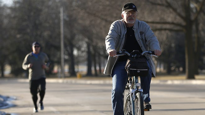 Ken Zimmer rides his bike through Lakeside Park Friday as temperatures rose into the upper 50s, 25 degrees above normal for mid-February. High temperatures in the 50s are expected for the Fond du Lac area through Wednesday.