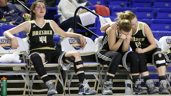 Dresden teammates Alex Sledd (44), Kasey Gallimore (4) and Mary Grace Davis (14) dejectedly look on as the clock winds down during their TSSAA Class A state quarterfinal against Summertown at the Murphy Center in Murfreesboro on Thursday, March 9, 2017.