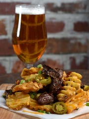 Loaded waffle fries mounded with barbecue beef, cheddar cheese, green onions, pickled jalapeños and sour cream are being offered at one of the street booths at the 20th annual Great Eldorado BBQ, Brews & Blues Festival.