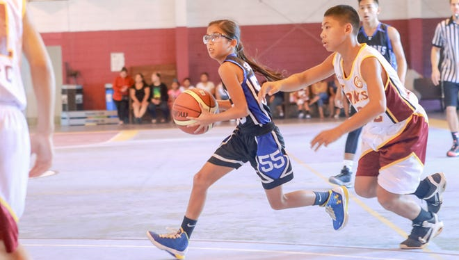 Alana Salas (55) of the Falcons dribbles evading a Hawks player.