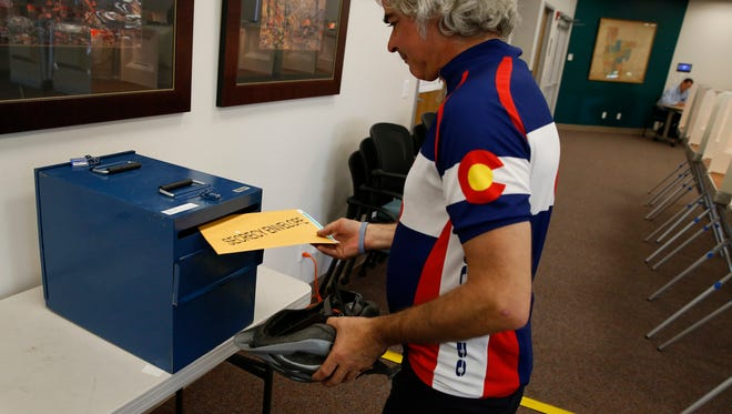 A voter places his ballot into a collection box after filling it in at a polling center, on state primary election day, in Boulder, Colo., Tuesday, June 28, 2016. (AP Photo/Brennan Linsley) ORG XMIT: COBL101
