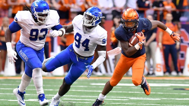 Syracuse running back Moe Neal (21) runs past MTSU defensive tackle Malik Manciel (93) and defensive end Tyshun Render (94) during a game last season.