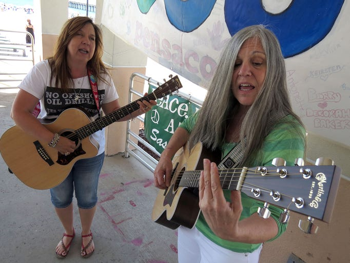 "Jo Billups and, right, Karen Harvill, the duo that goes by the name Sassafrass, perform their song ""Hands Across the Sand"" Saturday at the Gulfside Pavilion for the dozens of people gathering for the Hands Across the Sand demonstration on Pensacola Beach."