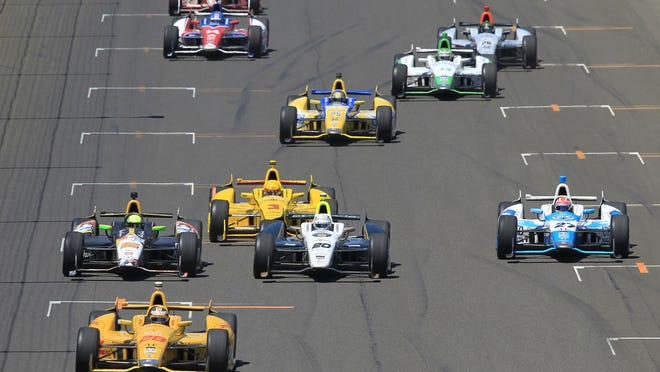 Cars bunch up behind Ryan Hunter-Reay, front on the second green flag restart late in the race at the 98th running of the Indianapolis 500 at the Indianapolis Motor Speedway on Sunday, May 25, 2014. As they headed into Turn One, Ed Carpenter, running in second (center) and James Hinchcliffe, right, crashed. The other cars at the front of the pack included Marco Andretti (at left behind Hunter-Reay) and Helio Castroneves (behind Carpenter).