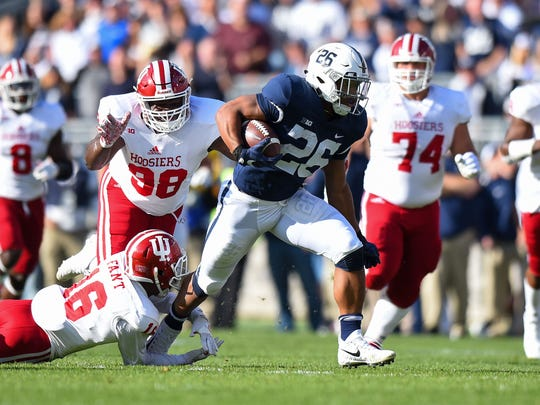 Penn State Nittany Lions running back Saquon Barkley (26) runs with the ball as Indiana Hoosiers defensive back Rashard Fant (16) and defensive lineman Jerome Johnson (98) defend during the first quarter at Beaver Stadium.