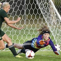 St. Cloud Cathedral's Megan Voigt passes the ball past Sauk Rapids' Brooke Lorentz in the first half Monday at Whitney Fields.