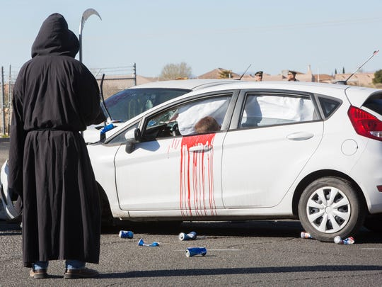 "A grim reaper stands near a mock drunken driving crash near Oñate High School on Thursday, March 15. The ""Shattered Lives"" production teaches students the dangers of DWI."
