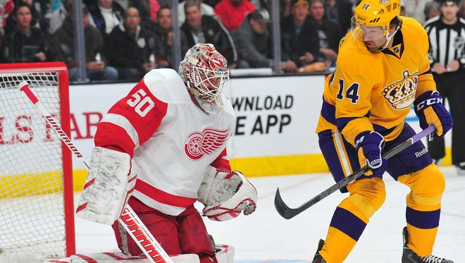 Los Angeles Kings right wing Justin Williams (14) plays for the puck  in front of Detroit Red Wings goalie Jonas Gustavsson (50) during the first period at Staples Center.