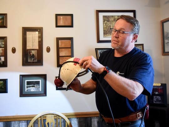 Sam Bennett demonstrates how a miners belt, light, and helmet all connect using Arthur Bennett Sr.'s helmet. Sam's father, Arthur, died in a mining accident and a friend returned the helmet to the family.