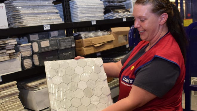 Dotti McCully, a kitchen designer at Lowe's Home Improvement in Pineville, shows some of the more popular kitchen backsplash tiles that people choose.