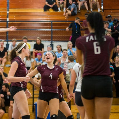 Teammates celebrate after Menomonee Falls junior Rachel Murphy (left) makes a kill against Nicolet during the Indian volleyball team's game against the host Knights on Aug. 24. The Indians won the game.