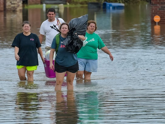 People make their way through a flooded area in Youngsville,
