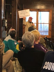 """A gentleman holds a sign reading """"DNR — Destroyer of Natural Resources?"""" at a public hearing Thursday night at Mounds State Park in Anderson, Ind."""