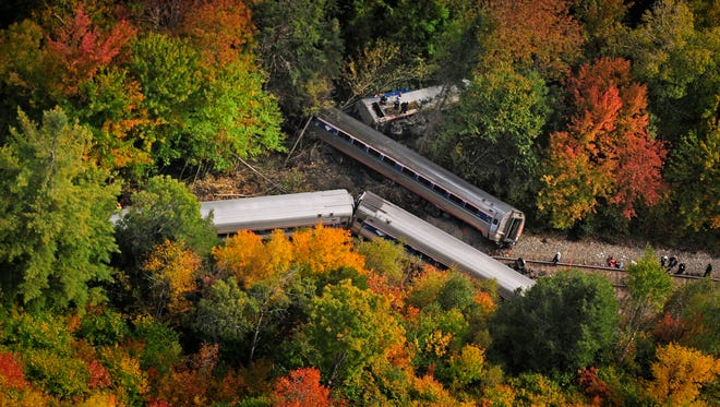 In this aerial photo railroad passenger cars from a derailed Amtrak passenger train are surrounded by foliage, Monday, Oct. 5, 2015, in Northfield, Vt. The train, the Vermonter, was headed from Vermont to Washington, D.C., when it apparently struck rocks that were on the tracks. No life-threatening injuries were reported. (