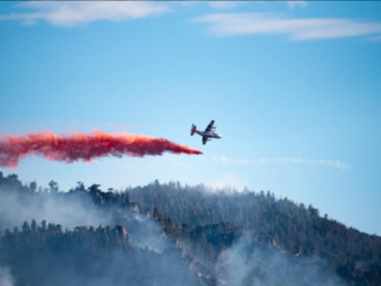 A firefighting plane drops retardant over the Saddle