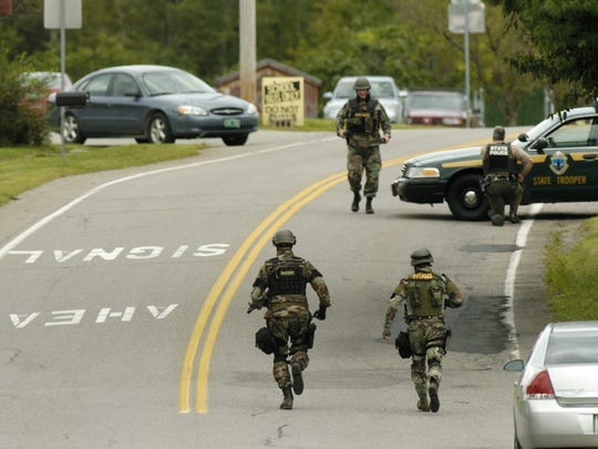 State police wearing camouflage and body armor move into position outside Essex Elementary School on Aug. 24, 2006.