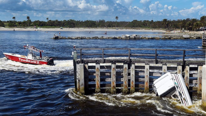 Two boats, a pontoon boat (right) and a TowBoatUS from Sebastian, capsized under the bridge at Sebastian Inlet State Park, Monday, Oct. 16, 2017. Several people went into the water as rescue efforts were underway. All passengers were recovered.