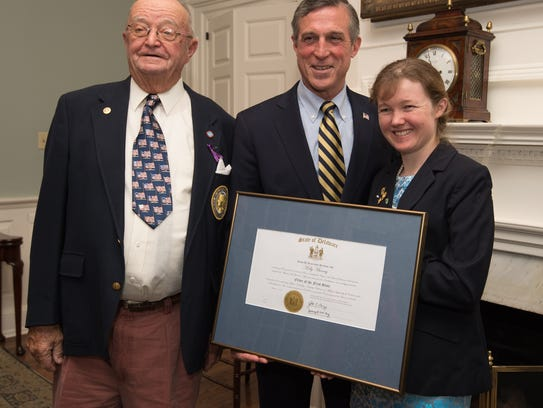 Governor John Carney presents an award of recognition