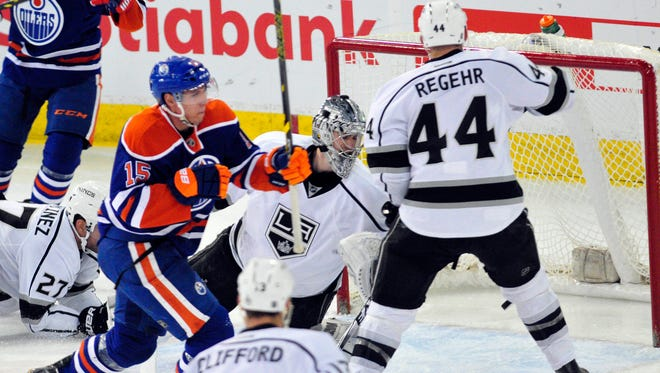 Edmonton Oilers right winger Tyler Pitlik (15) gets the puck past Los Angeles Kings goalie Martin Jones (3) and Kings defenceman Robyn Regehr (44) during the third period at Rexall Place.