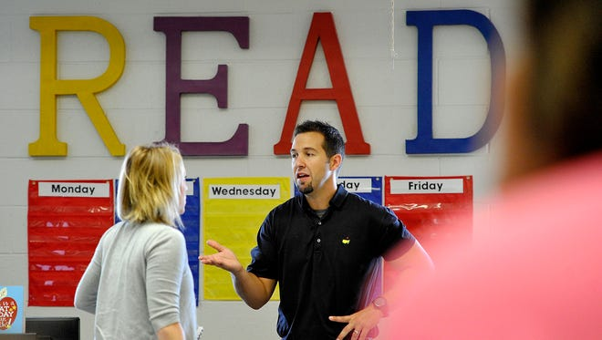 West Wilson Principal Chris Plummer talks with teachers in the library in preparation of students' return next week.