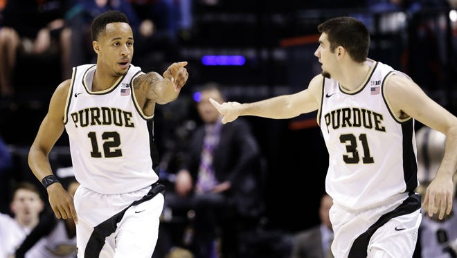 Boilermakers forward Vince Edwards (12) points to guard Dakota Mathias (31) thanking him for the assist that lead to a made 3-pointer against Illinois at Bankers Life Fieldhouse Friday.
