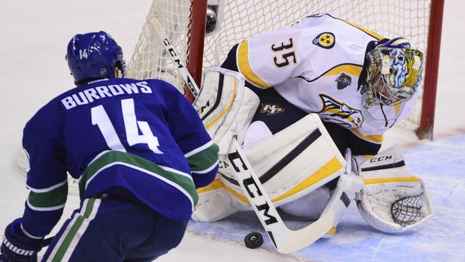 Predators goaltender Pekka Rinne (35) stops a shot by Canucks forward Alexandre Burrows (14) in the third period Saturday.