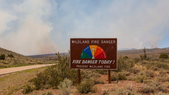 A wildland fire danger sign sits near Panguitch Lake with the Brian Head fire burning in the distance on Saturday, June 24, 2017.