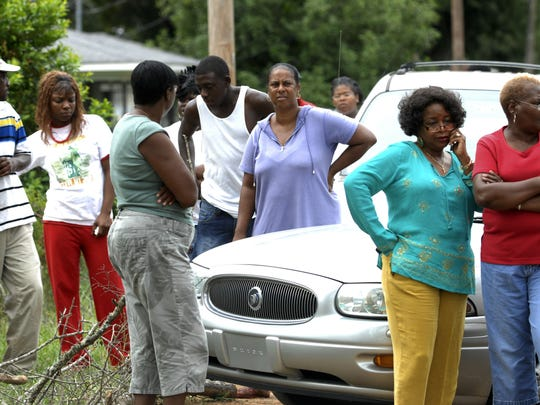 Friends and neighbors of Barry Shipp gather near Arnold's House of Style on L Street in 2007 as investigators canvassed the barber's murder scene.