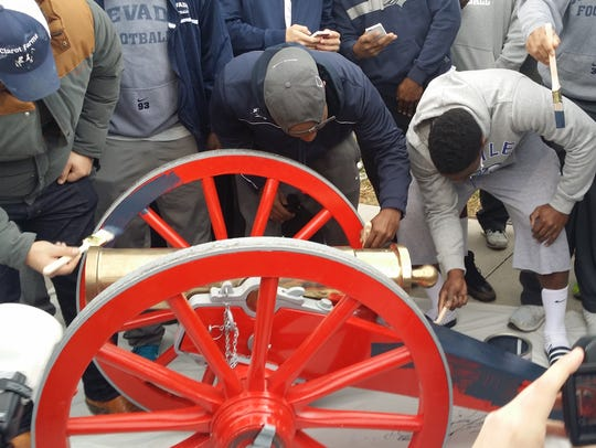 Nevada Wolf Pack football players paint Fremont Cannon