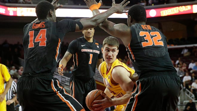 Southern California's Strahinja Gavrilovic, of Serbia, is defended by Oregon State's Daniel Gomis, left, and Jarmal Reid during the first half of an NCAA college basketball game, Saturday, Feb. 14, 2015, in Los Angeles.