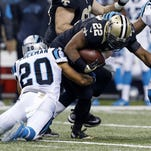 New Orleans Saints running back Mark Ingram (22) carries for a first down as he is tackled by Carolina Panthers free safety Kurt Coleman (20) and strong safety Roman Harper (41) Sunday in New Orleans.