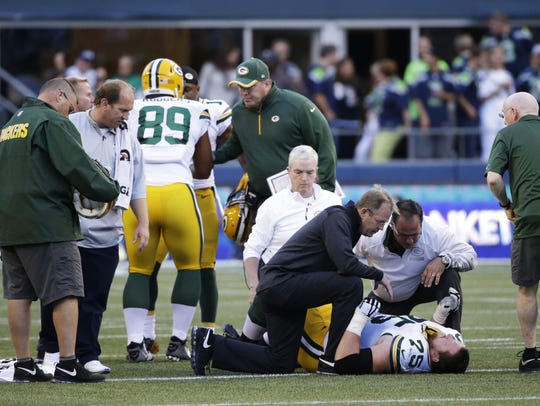 Dr. Patrick McKenzie, in black, checks on Packers tackle
