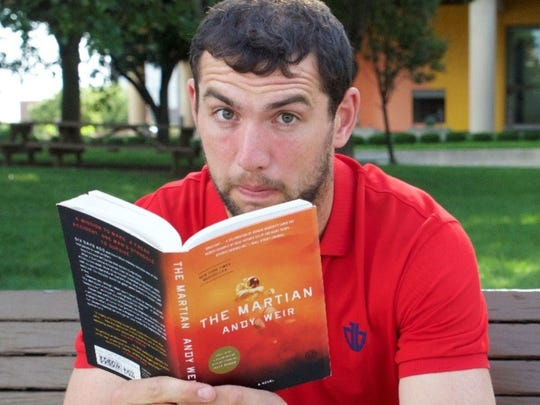 "Colts Quarterback Andrew Luck is shown reading ""The Martian,"" by Andy Weir, which was made into a movie. Luck was an engineering major at Stanford University."