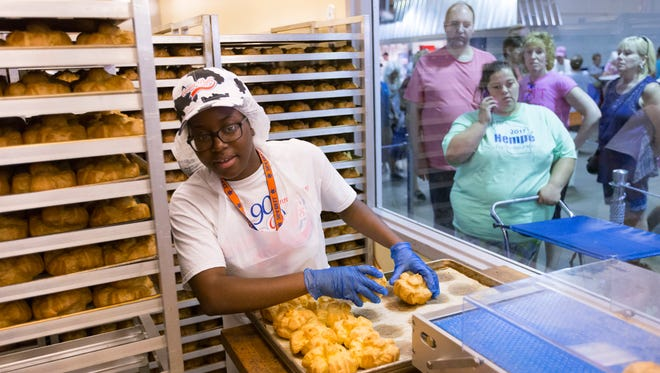 Cream puffs are loaded into a new machine that slices them, increasing the efficiency of workers in the dairy building at State Fair Park.