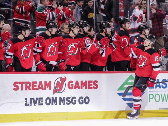 New Jersey Devils defenseman Steven Santini (16) celebrates his goal against the Dallas Stars with teammates during the first period at Prudential Center.