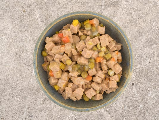 Stoneware bowl of lamb dog food on a concrete floor